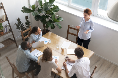 Female leader manager coach talking to employees group leading corporate meeting, diverse team people company staff listen to boss instructing interns planning work at office training, top view Standard-Bild - 120839407