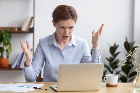 Femme d'affaires folle en colère et agacée regardant l'écran d'un ordinateur portable se sentant frustrée par un problème d'ordinateur cassé, de mauvaises nouvelles en ligne, un ordinateur portable lent bloqué, une lettre de courrier indésirable, une erreur Web, un mauvais site Web