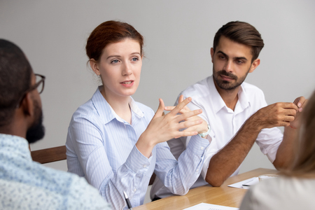 Confident female coach mentor leader speak at group training negotiate explain corporate strategy make offer, businesswoman manager teach staff instruct interns consult clients at team office meeting