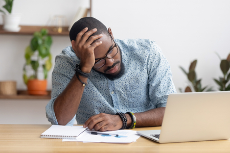 Zmęczony przygnębiony znudzony afrykański biznesmen sfrustrowany niepowodzeniem w biznesie bankructwo patrząc na laptopa czuję się wyczerpany ból głowy, zdenerwowany zestresowany czarny pracownik biurowy zaniepokojony problemami w pracy