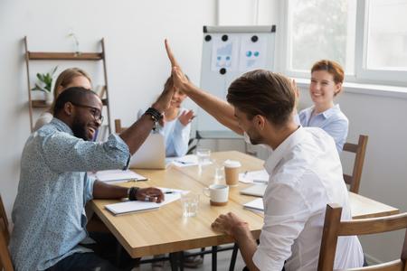Des collègues masculins heureux et diversifiés se donnent la main en donnant cinq coups pour célébrer le résultat d'un travail d'équipe réussi lors d'une réunion de bureau de groupe, obtenir le soutien de l'équipe, féliciter avec la récompense de la victoire du travail bien fait