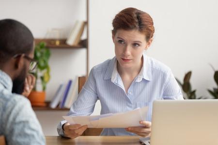 Wütende weibliche Chefin unzufrieden mit schlechtem Finanzergebnis im Bericht fordert Erklärung von gestresstem inkompetenten afrikanischen Mitarbeiter, der verärgerte Praktikantin wegen Fehlern bei Papierkram mit Konflikten bei der Arbeit schimpft. Standard-Bild