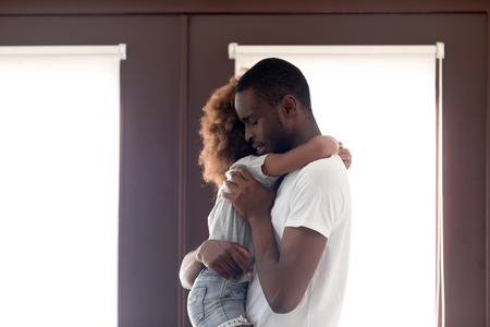 Sad African American man holding daughter in hands, saying goodbye before leaving for long business trip, standing in entrance hall at home, upset father embracing little girl, family separation