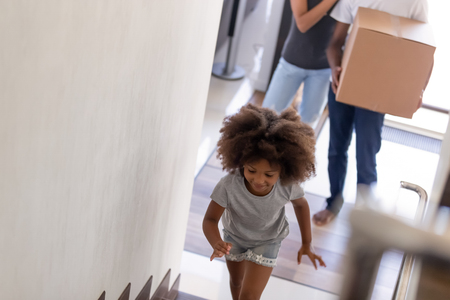 Happy African American family with daughter moving in new house, smiling little girl running up stairs, mother and father with cardboard box with belongings standing, mortgage, relocation concept