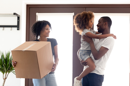 Happy African American family moving in new own house, mother with cardboard box with belongings standing in entrance hall, smiling father holding daughter in hands, relocation concept