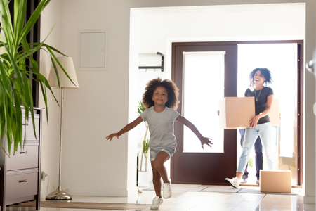 Happy African American family with cardboard boxes in new own home at moving day, excited little girl running in hall, smiling patents with belongings, relocation concept, mortgage