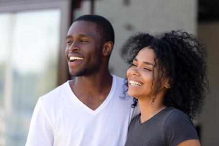 Lächelndes verliebtes afroamerikanisches Paar, das draußen zusammensteht, aufgeregter Mann und Frau, die wegschauen, sich glücklich über den Kauf eines neuen Hauses fühlen, zufriedene lachende Kunden, Nahaufnahme Standard-Bild