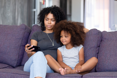 African American woman with daughter using phone together at home, sitting on sofa in living room, mother watching interesting cartoons with child, making selfie, video call, free time