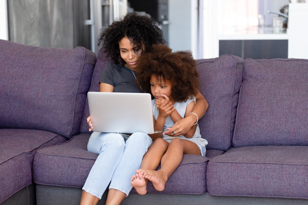 African American mother with little daughter using laptop together, sitting on comfortable sofa in living room, looking at computer screen, watching cartoons, making video call, shopping online