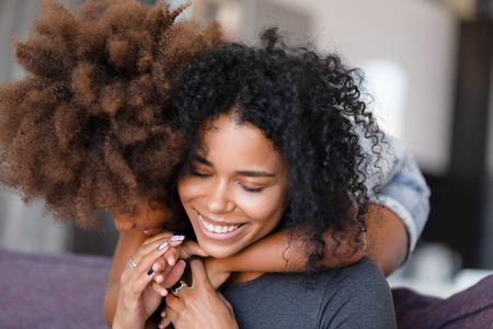 Close up smiling African American mother embracing with preschool daughter, sitting in living room on cozy sofa at home together, feeling happy, family warm relationships, showing support and love