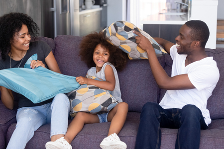 Happy African American family playing together, laughing mother and father pillow fighting with little preschooler daughter, sitting on sofa in living room, free weekend at home, good relations