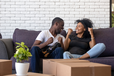 Excited African American couple in love celebrating moving day, sitting together on sofa in living room in new house, handsome black man with dog at knees feeling happy about relocation