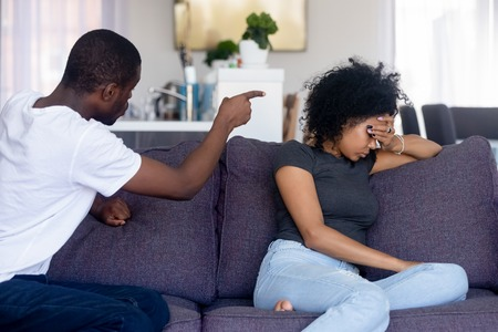Angry African American man quarreling, emotionally shouting at upset woman, sitting on sofa at home, irritated husband blaming sad frustrated woman feeling offended, family conflict, break up
