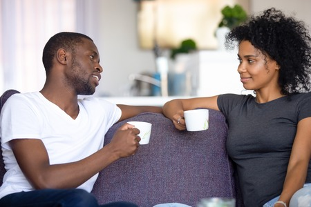 Satisfied African American couple talking, drinking coffee at home, smiling man and woman sitting on cozy sofa at home, having pleasant conversation, spending weekend together, resting Stok Fotoğraf