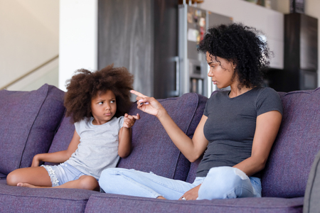 Upset African American woman and little girl quarreling at home, blaming each other, sitting together on sofa in living room, family conflict between offended mother and daughter Stock Photo