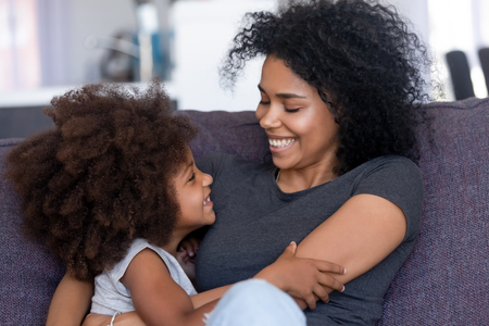 Close up smiling African American mother and daughter embracing, sitting on cozy sofa, looking at each other, having fun together, warm relationships between parent and child concept