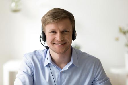 Hoofd geschoten portret van een knappe glimlachende man met een hoofdtelefoon op kantoor die naar de camera kijkt. Introductie callcenter. Gelukkig werknemer op werkplek. Mensen op werk. Priveondernemer. Video-interview
