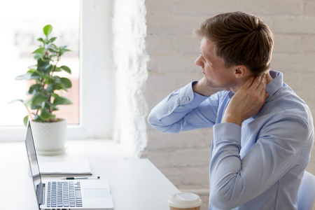 Tysiącletni zmęczony mężczyzna z bólem szyi. Mężczyzna dotykający masujący szyję siedzący w miejscu pracy, cierpiący na dyskomfort długie godziny siedzącego trybu życia, koncepcja nadgodzin, mięśnie wyczerpane przepracowaniem