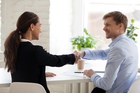 Happy millennial candidate shaking hands with employer after job interview, employment and business meetings, first impression, introduction, negotiation, recruiting, hr, bank service concept