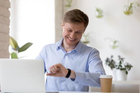 Hombre de negocios que trabaja, revisa el reloj de pulsera o el reloj mientras está sentado en un escritorio en la oficina y sonríe, administra el tiempo, terminó la última tarea justo a tiempo, saliendo de casa temprano el viernes Foto de archivo
