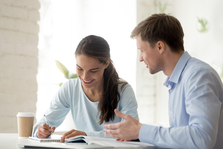 Enseignant et élève s'amusant à apprendre. Une écolière heureuse écrit des notes dans un cahier. Un professeur souriant explique le sujet au jeune étudiant. Fille prenant des cours supplémentaires. Collègues au travail au bureau