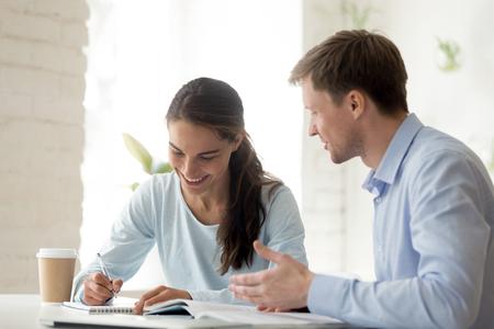 Nauczyciel i uczeń zabawy w nauce. Szczęśliwa uczennica pisze notatki w notatniku. Uśmiechnięty profesor wyjaśnia temat młodemu studentowi. Dziewczyna biorąc dodatkowe zajęcia. Współpracownicy w pracy w biurze