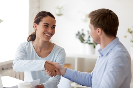 Successful business negotiations with handshake between two partners. Smiling people. Insurance, real estate agent, financial advisor, banker interview with client. Startup investor meeting concept