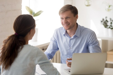 Cheerful man and woman at business meeting. Insurance agent, financial advisor, real estate agent, bank worker interview with client. Startup investor business meeting concept. Successful negotiations Banque d'images - 121256600