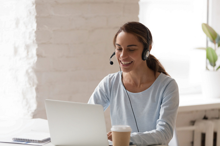 Beautiful smiling woman working in headphones at office. Call center introduction. Happy employee at workplace. People at work at home. Video job interview, language course, class concept