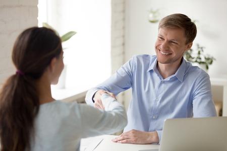 Trattative di successo assicurano l'affare. Assicurazione, agente immobiliare, consulente finanziario, colloquio bancario con il cliente. Concetto di riunione d'affari dell'investitore di avvio. L'uomo sorridente stringe la mano alla donna d'affari