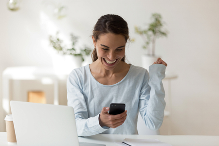 Happy Excited woman looking at phone screen smiling, got text message on gadget. Social network, media, chat, app concept. winner girl achieved new opportunity promoted via telephone. People lifestyle