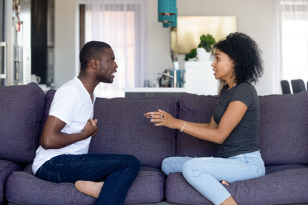 Unhappy African American couple quarreling, sitting on sofa at home, upset woman shouting, blaming black man, emotionally arguing, family conflict between wife and husband, break up Imagens