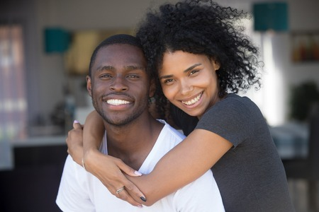 Head shot portrait of smiling African American couple in love, attractive girlfriend piggyback boyfriend, looking at camera, excited wife embracing, hugging husband, good date, romantic relationship 写真素材