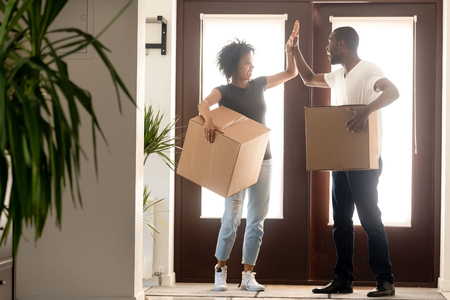 Excited African American couple giving high five, standing in hall of hew home, holding cardboard boxes with belongings, celebrating relocation, successful deal, moving day, buying real estate Stock Photo - 121256717