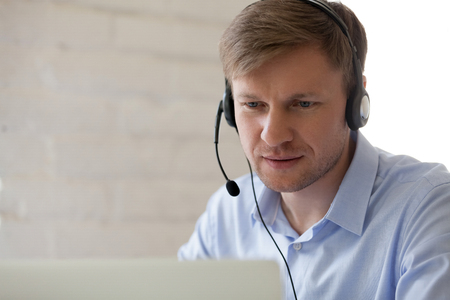 Happy millennial support team hotline worker using laptop wearing headphones at workplace. Young businessman consulting client online, remote study, taking video course learning language at home