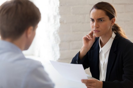 HR manager looking suspiciously at job candidate reading cv resume of male applicant. Skeptic woman is unpleasantly surprised by no good results. Bad first impression, reject View over the shoulder