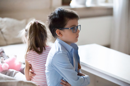 Upset sister and brother sitting angry after fight. Boy and girl turn back on each other after conflict. Kids relationship, children behavior, interacting, conversation problem, childhood concept Imagens