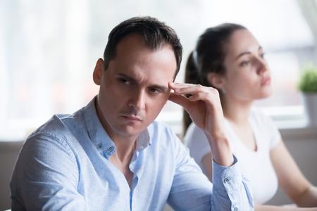 El hombre y la mujer obstinadamente no hablan sintiéndose ofendidos por tener una pelea en casa. Familia tras pelea, macho en foco. Pensamientos sobre ruptura, divorcio. Problemas de relación, concepto de conflicto de intereses