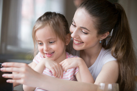 Mother and daughter having fun playing smartphone together. Mommy using gadget entertain little girl, laughing watching funny video on telephone screen. Happy family leisure time, technology concept Stock Photo