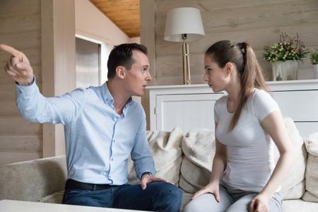Jeune homme et femme ayant un combat émotionnel à la maison. Conflit de couple millénaire, mari criant à la femme pointer sur la porte avec le doigt. Problème familial, crise relationnelle, divorce, concept de rupture