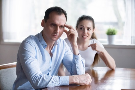 Couple in fight, man in focus. Depressed husband with headache ignoring screaming irritated woman. Big trouble, problem because of misunderstanding, conflict in family. Hard relationship concept
