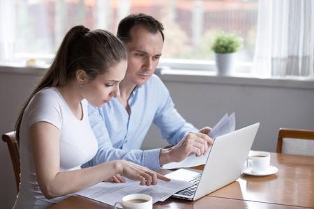 Pareja milenaria estudiando contrato para nueva casa antes de firmar. Marido y mujer comprobando documentos para comprar una propiedad. Compra de bienes raíces, propietario, préstamo, crédito, hipoteca, alquiler, concepto de inquilino