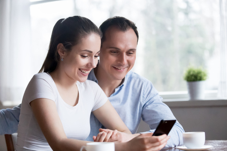 Smiling millennial couple reading message, news on phone. Man and woman surfing internet, browsing tape social networks, checking email, chatting, watching video, having video conference with friends