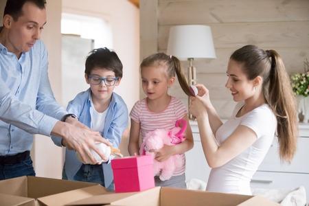 Familie hat Spaß beim Auspacken am Umzugstag in ein neues Haus. Glückliche Menschen nehmen ihre Sachen aus den Kartons und spielen mit Kinderspielzeug. Die ganze Familie verbringt Zeit zusammen. Hypothek, Darlehen, Umzugskonzept