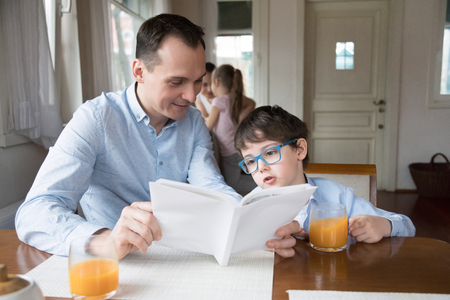 Father and son reading book together at dining room. Family leisure time concept, happy family. Husband and brother making home task while wife and daughter cook breakfast at home on weekend morning