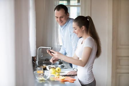 Happy young couple watching video on smartphone while cooking in kitchen at home. Attractive millennial wife laughing showing husband funny clip. Gadget addiction concept. People interacting at home