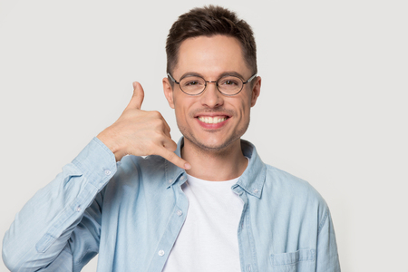 Smiling Caucasian young man in glasses isolated on grey studio background show call me gesture looking at camera, happy European male in spectacles talk on imaginary cell. Mobile communication concept Banco de Imagens