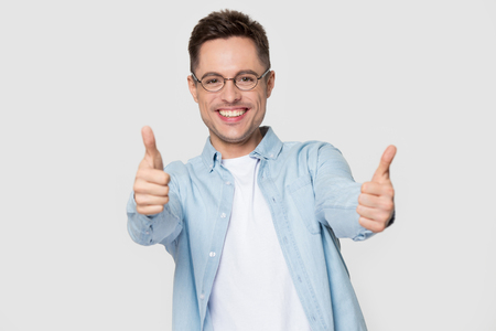 Excited young Caucasian man student in glasses and shirt show thumbs up recommending service, happy male client in spectacles isolated on grey studio background give good positive recommendation
