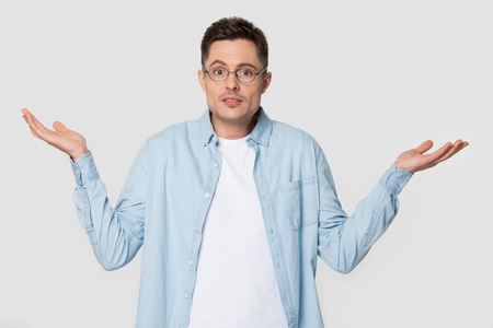 Doubtful Caucasian male in glasses feel at loss lift hands in confusion unsure about problem, puzzled European man in spectacles isolated on grey studio background shrug shoulders, confused or baffled Stock Photo