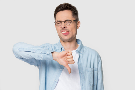 Dissatisfied Caucasian male customer in glasses and shirt isolated on grey studio background show thumb down, unhappy young man in spectacles dislike service, not recommending or advice